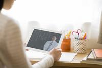 タブレットPCを見て勉強をする女子学生