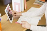 タブレットPCを使用して勉強をする女子学生の手元