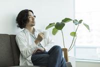 ソファーに座ってコーヒーを飲む男性