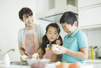 キッチンで玉ねぎの皮を剥く母親と子供たち
