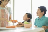 キッチンで料理をする母親に寄り添う子供たち