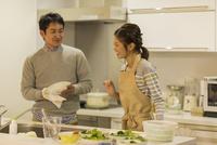 キッチンで調理をする夫婦