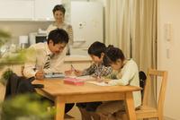 子供たちの勉強を見る父親