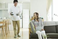 ソファーに座る妻とコーヒーを運ぶ夫 10367009534| 写真素材・ストックフォト・画像・イラスト素材|アマナイメージズ