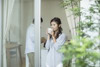 窓辺で外を眺める女性