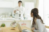 キッチンに立つ夫と会話をする妻