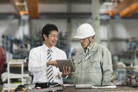 タブレットPCを見ながら打ち合わせをする作業員とビジネスマン 10367009717| 写真素材・ストックフォト・画像・イラスト素材|アマナイメージズ