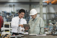 タブレットPCを見ながら打ち合わせをする作業員とビジネスマン 10367009750| 写真素材・ストックフォト・画像・イラスト素材|アマナイメージズ