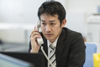 デスクで電話をするビジネスマン