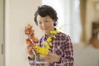 花瓶に花を飾るシニア女性