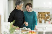 キッチンで調理をするシニア夫婦