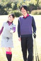 ゴルフクラブを持ってグリーンで指さす若いカップル 10373000409| 写真素材・ストックフォト・画像・イラスト素材|アマナイメージズ