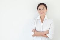 腕を組んで微笑む中年女性 10373002428| 写真素材・ストックフォト・画像・イラスト素材|アマナイメージズ