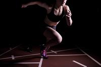黒バックで走る女性 10373017037| 写真素材・ストックフォト・画像・イラスト素材|アマナイメージズ