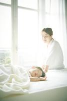 ベッドの上でお昼寝する赤ちゃんをお母さんが優しく見つめている
