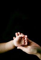 黒バックに赤ちゃんとお母さんの手