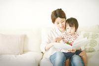 お母さんが赤ちゃんに本を読み聞かせている