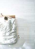 白い床の寝室にあるベットで起床した女性