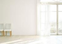 窓辺の白い壁と床に置いてある椅子二脚