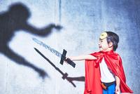 悪者と闘うちびっこスーパーマン 10387002363| 写真素材・ストックフォト・画像・イラスト素材|アマナイメージズ