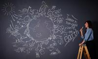 黒板に描かれた地球の絵に向かってマイクを持つ女性