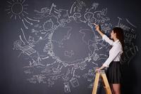 黒板に地球の絵を描く女子高生