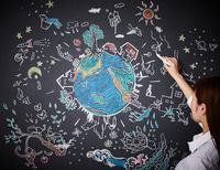 黒板に地球を描く女性