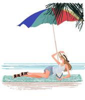 浜辺でビーチパラソルの下で寝転び本を読む女性