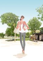 春のパリの公園を本を抱えて歩く女性