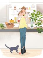 キッチンでフルーツを食べる女の子と足元で遊ぶ猫