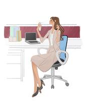 オフィスのデスクに座り保湿スプレーをする女性