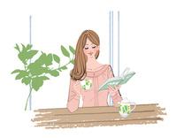 リビングで本を読みながら紅茶を飲む女性