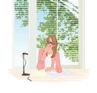 窓辺の机に座りペンで書類を書く眼鏡をかけた女性