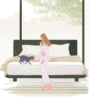 ベッドに座り猫と遊ぶパジャマを着た女性