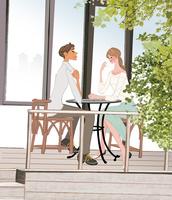ウッドデッキでテーブルに座りお茶を飲むカップル