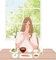 リビングで和食の朝食を食べようとする箸を持つ女性