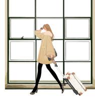 スーツケースを引いて歩くコートを着た女の子