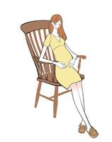 出産を控えて椅子に座るマタニティーワンピースの女性