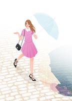 雨上がりの街を傘を差して歩く女性