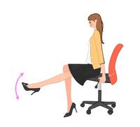 オフィスで椅子に座り脚を上下させる運動をする女性