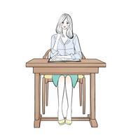 机に座り勉強する女性