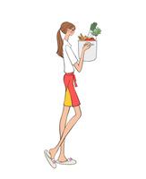 キッチンで料理をしようと野菜の入った鍋を持つ女性