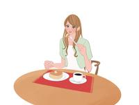 テーブルに座りホットーケーキを食べる女性