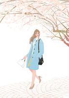 桜の木の下を歩く買い物帰りのコートを着た女の子