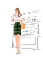 カフェスタンドの前に立ちコーヒーを手にする女の子
