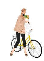 自転車で買い物をする秋の装いの女性