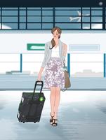 空港でスーツケースを引いて歩く女性