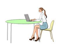 オフィスのテーブルでノートパソコンで仕事をするOLの女性