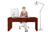 オフィスでデスクに座りパソコンで仕事しながらスマホで話す女性