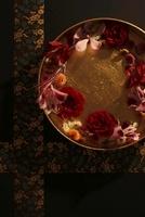 黒い紙と和紙のクロスラインを背景に金の丸い器に花と水引 10405000269| 写真素材・ストックフォト・画像・イラスト素材|アマナイメージズ